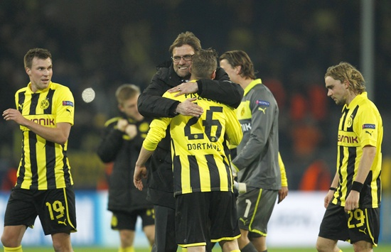 Borussia Dortmund's coach Juergen Klopp hugs his players