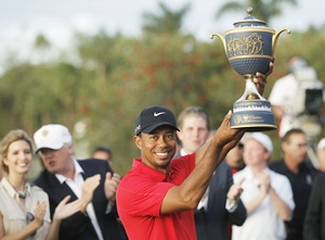 Tiger Woods hoists the Gene Sarazen Trophy