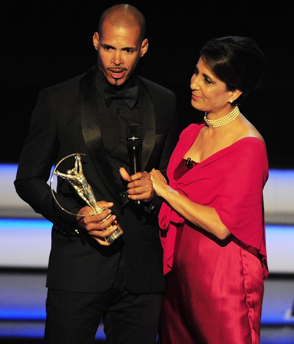 Athlete Felix Sanchez accepts his award from Laureus Academy Member Nawal El Moutawakel
