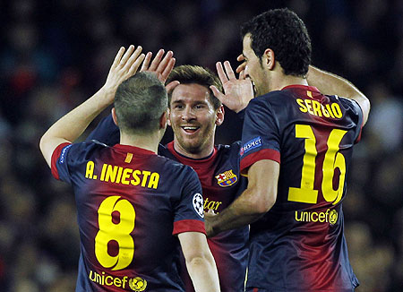 Barcelona's Lionel Messi (centre) celebrates victory over AC Milan with teammates Andres Iniesta (left) and Sergio Busquets