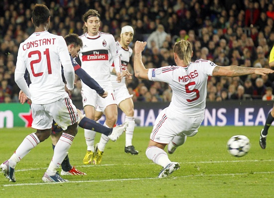 Barcelona's Lionel Messi (second left) scores his second goal past AC Milan's Philippe Mexes (right)
