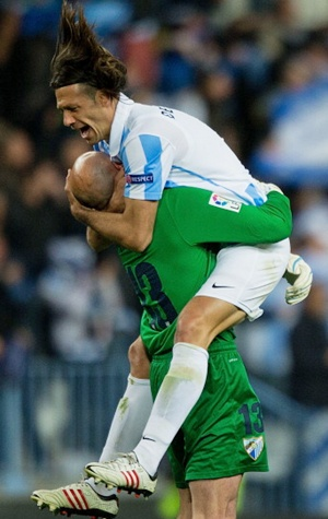 Martin G. Demichelis (R) of Malaga CF celebrates their first goal scored by his teammate Isco with goalkeeper Wilfredo Caballero 
