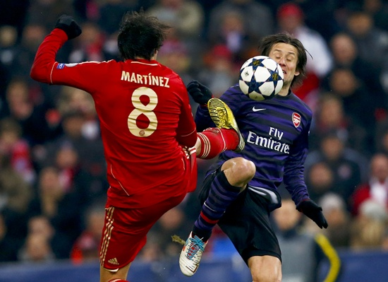 Arsenal's Tomas Rosicky receives a kick by Bayern Munich's Javi Martinez