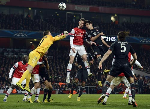 Arsenal's goalkeeper Wojciech Szczesny (L) and Laurent Koscielny (C) challenge Bayern Munich's Javi Martinez during their Champions League soccer match