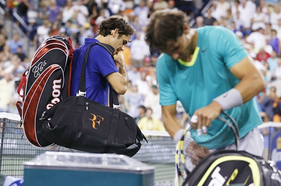 Roger Federer (left) of Switzerland leaves the court after losing to Rafael Nadal of Spain