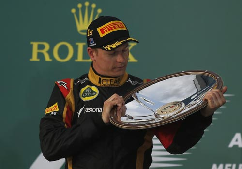 Lotus Formula One driver Kimi Raikkonen of Finland looks at his trophy after winning the Australian F1 Grand Prix at the Albert Park circuit in Melbourne