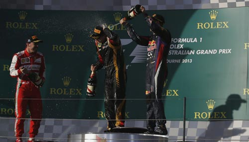 Red Bull Formula One driver Sebastian Vettel of Germany sprays champagne on Lotus Formula One driver Kimi Raikkonen of Finland (C), as Ferrari Formula One driver Fernando Alonso of Spain (2nd L) looks on after the Australian F1 Grand Prix