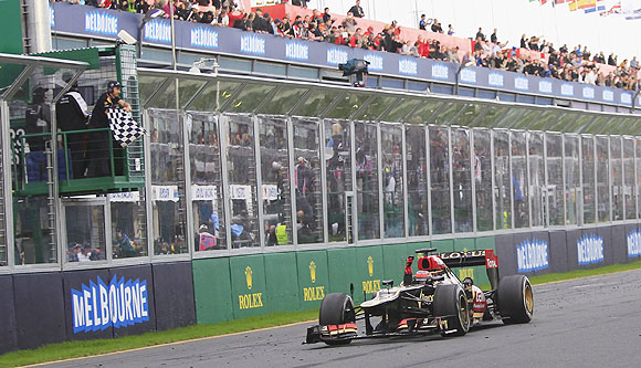 Lotus Formula One driver Kimi Raikkonen takes the chequered flag as he wins the Australian F1 Grand Prix at the Albert Park circuit in Melbourne Mon Sunday
