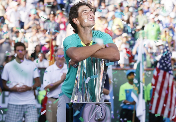 Rafael Nadal of Spain smiles as he leans on his trophy