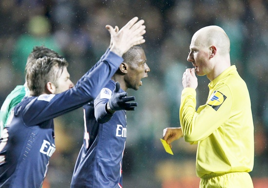 David Beckham (right) of Paris St Germain reacts as referee Antony Gautier (right) delivers a yellow card to team mate Blaise Matuidi