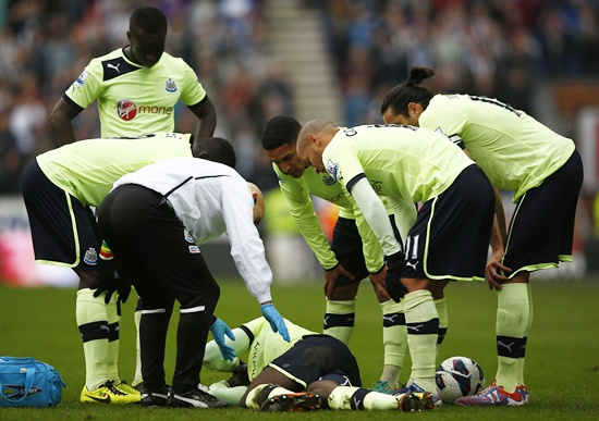 Newcastle United players look at their injured teammate Massadio Haidara