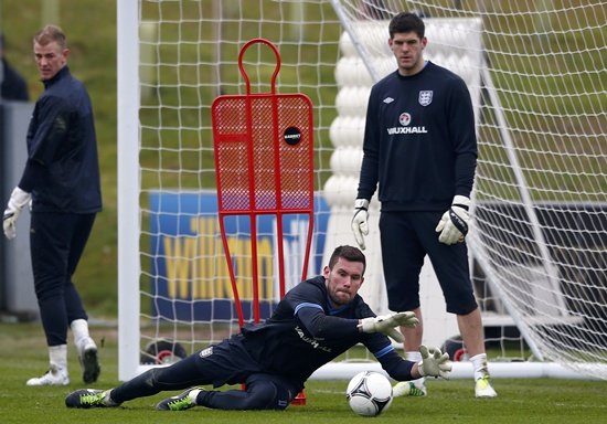 England's Ben Foster makes a save during a training session
