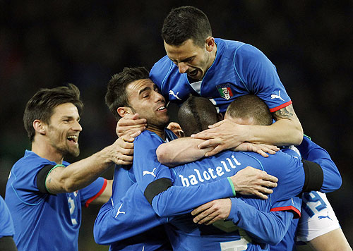 Italy players celebrate with Mario Balotelli (centre) after scoring the equaliser during their international friendly against Brazil at the Stade de Geneve in Geneva on Thursda