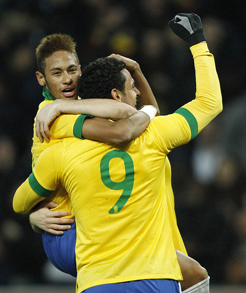 Brazil's Neymar (left) celebrates with teammates Fred and Oscar (hidden) after the latter scored the second goal during their international friendly against Italy at the Stade de Geneve in Geneva on Thursday