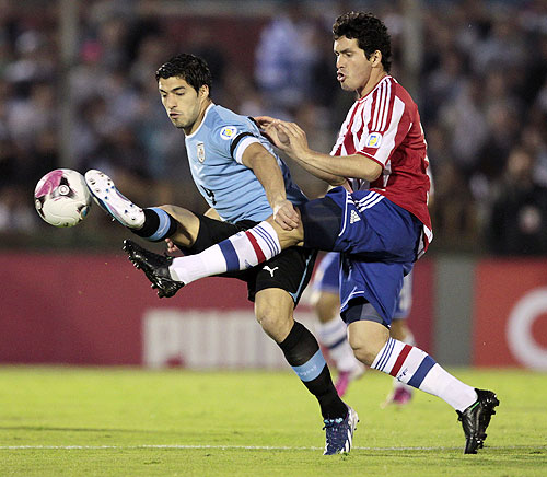 Paraguay's Cristian Riveros (right) and Uruguay's Luis Suarez vie for possession during their 2014 World Cup qualifying match in Montevideo on Friday