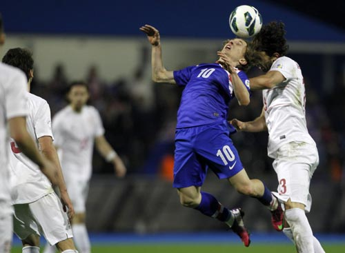 Ivan Radovanovic of Serbia (R) challenges Luka Modric of Croatia