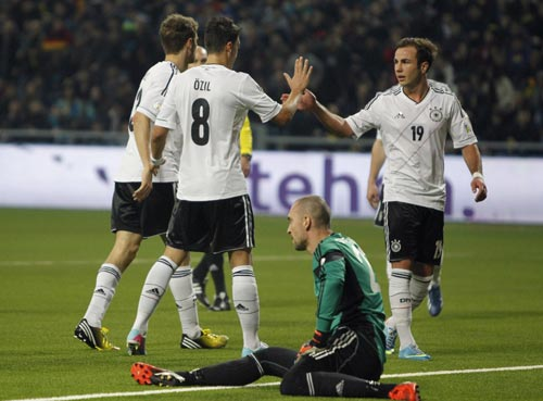 Germany's national soccer team players celebrate a goal next to Kazakhstan's goalkeeper Andrei Sidelnikov