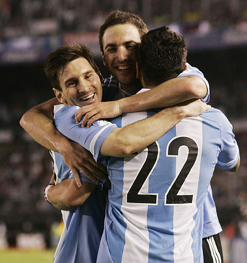 Argentina's Gonzalo Higuain (centre) celebrates with teammates Leonel Messi (left) and Ezequiel Lavezzi after he scored their third goal against Venezuela in a 2014 World Cup qualifying match in Buenos Aires on Friday
