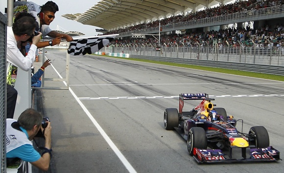 Red Bull driver Sebastian Vettel of Germany takes the chequered flag