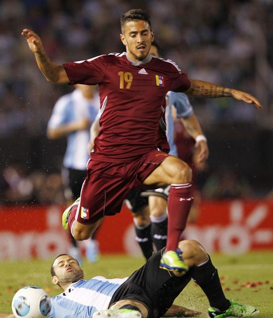 Venezuela's  Frank Feltscher (top) jumps over Argentina's Javier Mascherano
