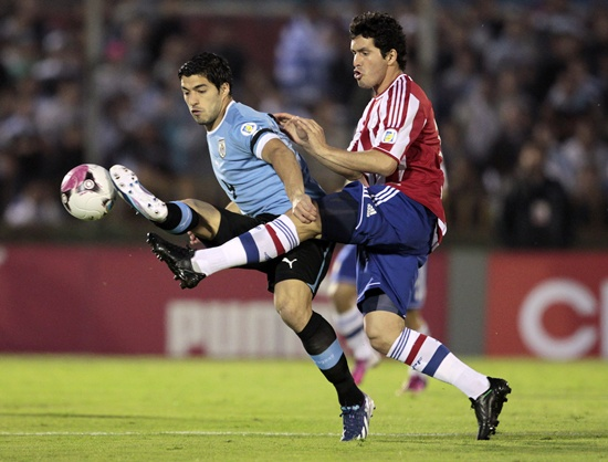 Paraguay's Cristian Riveros (right) fights for the ball with Uruguay's Luis Suarez
