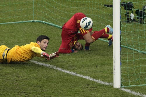 Spain's Pedro Rodriguez Ledesma (R) scores against France's Hugo Lloris (L) during their 2014 World Cup qualifying soccer match at the Stade de France stadium