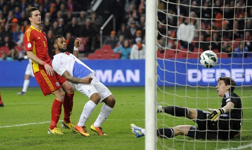 Jeremain Lens (C) of the Netherlands scores a goal past Romania's Florin Gardos and goalkeeper Costel Fane Pantilimon during their 2014 World Cup qualifying soccer match