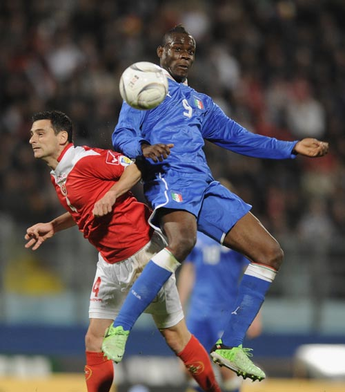 Mario Balotelli of Italy and Gareth Sciberras of Malta compete for the ball during the FIFA 2014 World Cup qualifier match between Malta and Italy