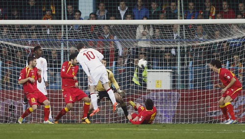 England's Wayne Rooney (C) heads to score against Montenegro during their 2014 World Cup qualifying soccer match at the City Stadium