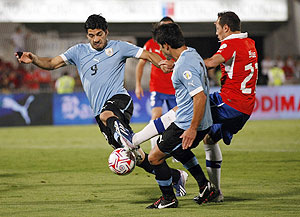 Uruguay's Luis Suarez (left) is challenged by Chile's Marcelo Diaz (right) during their 2014 World Cup qualifying match in Santiago on Tuesday