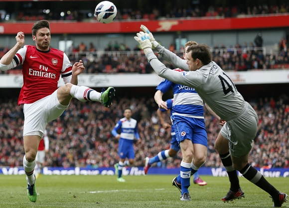 Arsenal's Olivier Giroud (left) challenges Reading's goalkeeper Stuart Taylor