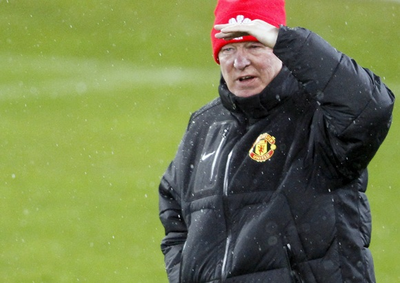 Manchester United manager Alex Ferguson stands in the rain during a team training session