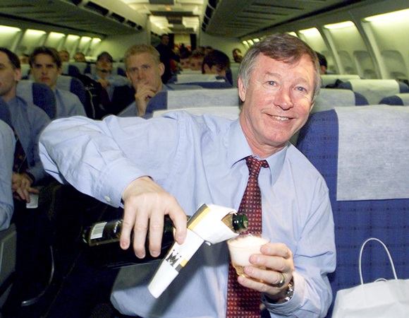Manchester United manager Alex Ferguson celebrates his team's   victory over FC Juventus with a champagne toast on the return flight from Turin to Manchester
