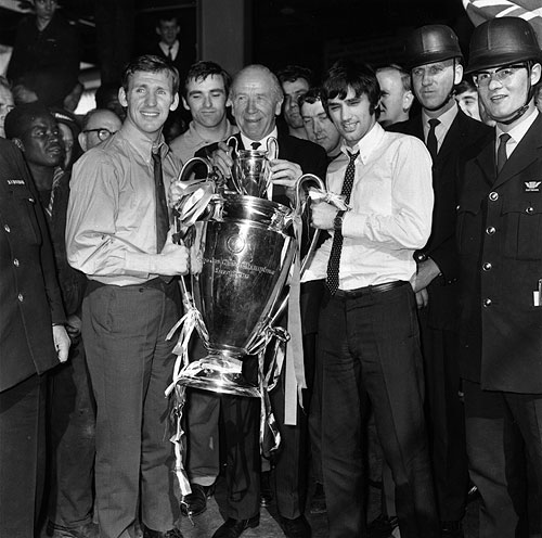 Manchester United manager Matt Busby (centre) holding the European Cup trophy with players Pat Crerand (left) and George Best, at Euston Station, on their way back to Manchester after beating Benfica 4-1 in the final at Wembley. On the right are security men who will guard the trophy during the journey on 30th May, 1968