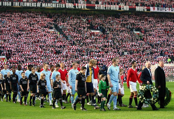 The Manchester United team (red) and Manchester City teams enter the pitch