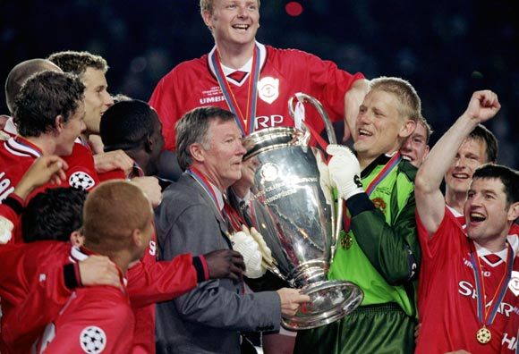 Alex Ferguson celebrates with his team after winning the Champions League in 1999