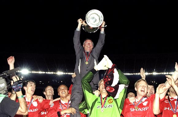 Alex Ferguson celebrates with his team after winning the Champions League trophy in 1999