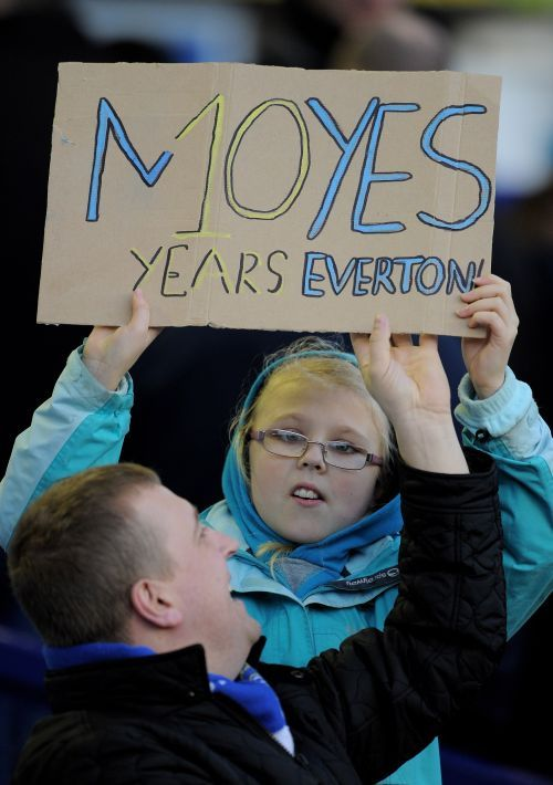 A fan holds a sign acknowledging Everton Manager David Moyes' completion of 10 years