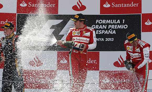 Fernando Alonso of Spain (centre) celebrates on the podium with second-place Lotus Formula One driver Kimi Raikkonen of Finland (left) and third-place Ferrari Formula One driver Felipe Massa of Brazil after the Spanish F1 Grand Prix on Sunday