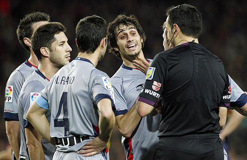 Osasuna's Alejandro Arribas (C) argues with the referee