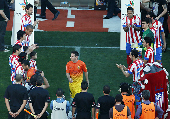Atletico Madrid's players greet Barcelona's Lionel Messi (centre) as he walks onto the pitch before their La Liga match at Vicente Calderon stadium in Madrid on Sunday