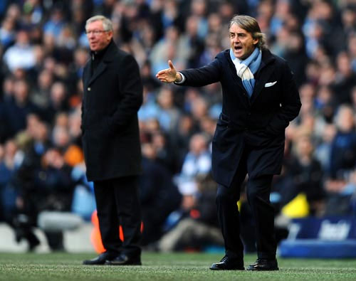 Manchester City manager Roberto Mancini with United manager Alex Feguson in the background