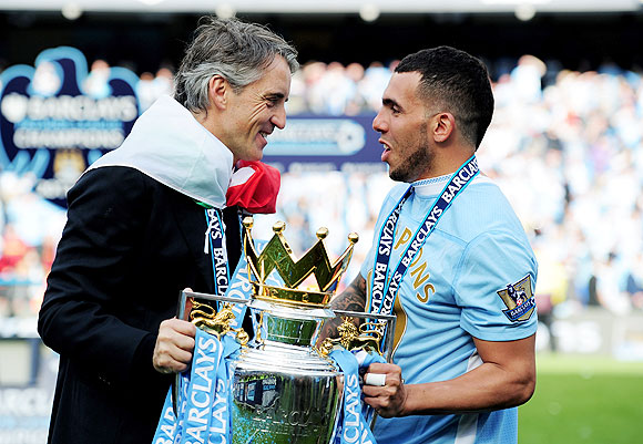 Roberto Mancini the manager of Manchester City and Carlos Tevez with the EPL trophy