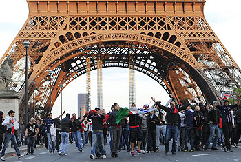 Fans gesture as they face riot Gendarmes in front of the Eiffel Tower on Monday
