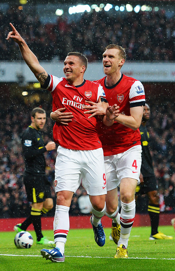 Lukas Podolski (left) of Arsenal celebrates with teammate Per Mertesacker (right) after scoring against Wigan Athletic on Tuesday
