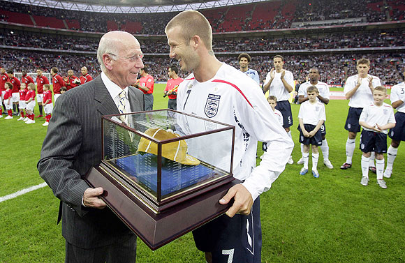 England's David Beckham (right) receives his 100th cap from Sir Bobby Charlton before the team's international friendly against the US at Wembley Stadium in London May 28, 2008