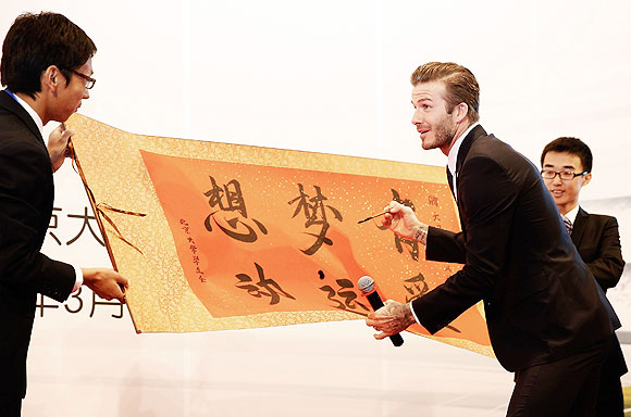 David Beckham learns Chinese calligraphy during a visit to Peking University on March 24, 2013 in Beijing, China. David Beckham visited the country at the invitation of the China Football Association as China's first international ambassador