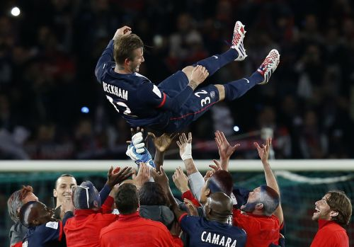 Paris Saint-Germain players throw David Beckham in the air at the end of their team's French Ligue 1 soccer match against Brest at the Parc d