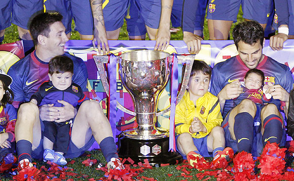 Lionel Messi and his son Thiago sits next to teammate Cesc Fabregas and his infant daughter Lia during the trophy presentation ceremony at the Camp Nou on Sunday