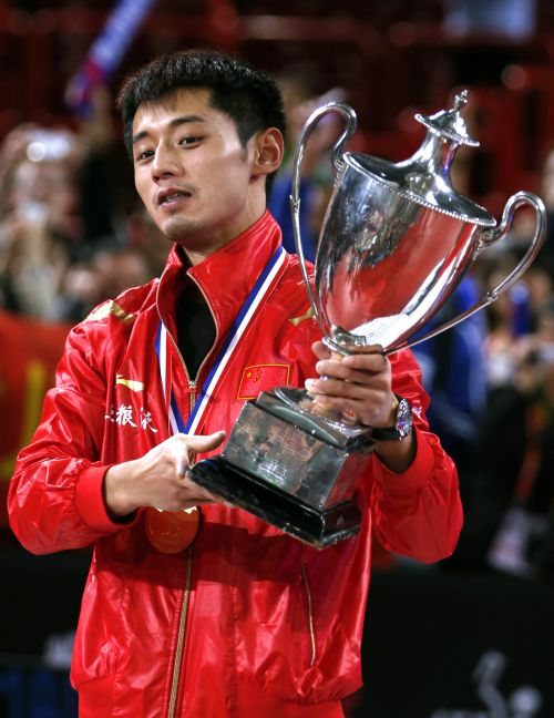 China's Zhang Jike holds up the trophy he won after the men's singles final at the World Team Table Tennis Championships in Paris